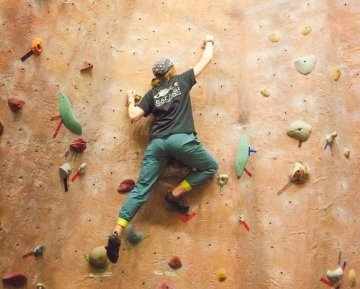 A student carefully makes their way up a climbing wall.